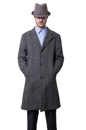 A person dressed in a gray overcoat and a gray hat that is almost completely hiding his eyes. Hands in coat pockets. Isolated on white background. photo