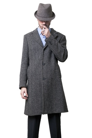 A person dressed in a gray overcoat and a gray hat that is almost completely hiding his eyes. Smoking a cigarette. Isolated on white background.