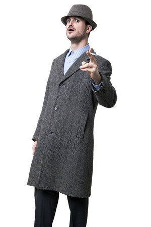 intimidating: A person dressed in a gray overcoat and a gray hat shading his eyes. He seems to be angry, Pointing his hand holding a cigarette and wearing an intimidating facial experssion Isolated on white background. Stock Photo