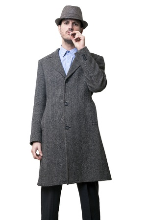 A person dressed in a gray overcoat and a gray hat. His left hand holding a cigarette to his lips, taking a puff while staring to the camera with a serious expression on his face. Isolated on white background.