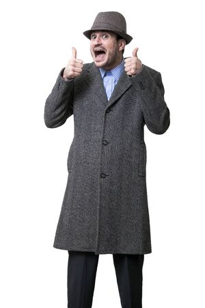 outgoing: An adult male wearing an overcoat and a hat looking at the camera with an outgoing pleasure, raising both thumbs up. Isolated on white background.