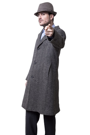 intimidating: A person dressed in a gray overcoat and a gray hat. He seems to be angry, his finger to the camera and wearing an intimidating facial experssion Isolated on white background. Stock Photo