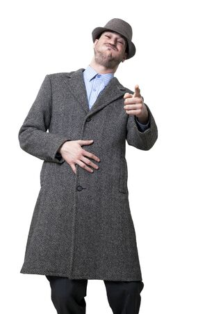 A young adult male wearing an overcoat and a maching hat, looking and pointing at the camera bursting with laughter. Isolated on white background. photo