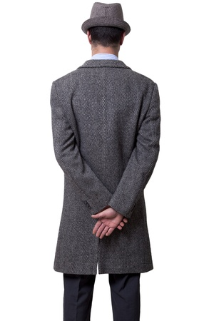 A person dressed in a gray overcoat and a gray hat standing with his back to the camera, holding his right hand over his left one.  Isolated on white background. photo