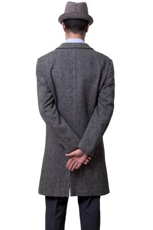 Una persona vestida con un abrigo gris y un sombrero gris de pie, de espaldas a la cámara, sosteniendo su mano derecha sobre el izquierdo. Aislado sobre fondo blanco.