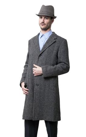 sarc�stico: Una persona vestida con un abrigo gris y un sombrero gris con una ligera sonrisa sarc�stica en su rostro. Su mano izquierda sostiene el escudo. Aislado sobre fondo blanco.