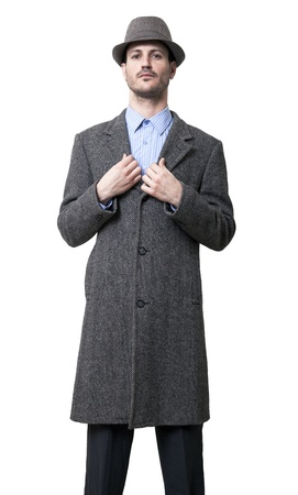 boastful: A young adult dressed in a gray overcoat and a gray hat with a slight confident smile on his face, straightening his coat. Isolated on white background. Isolated on white  Stock Photo