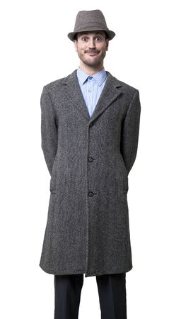 maladroit: Un jeune adulte de sexe masculin portant un manteau et un chapeau assorti, le sourire et les yeux grands ouverts � regarder d'une mani�re maladroite � la cam�ra. Isol� sur fond blanc.