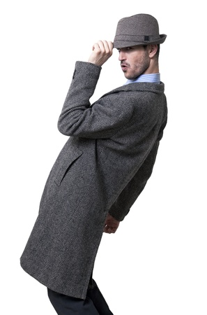 An adult male wearing an overcoat and lowering his hat a little,  in a greeting gesture. Standing sideways to the camera and looking to the lens, his knees bent andleaning back, as if in the middle of a dance. Isolated on white background.