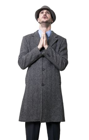 pleas: A young adult malewearing a gray overcoat and hat. Hes looking upwards with a pleas in his eyes, his hands put together in a pleading gesture. Isolated on white background.