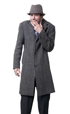 chuckling: A young adult male wearing a gray overcoat and a matching hat, standing and looking at the camera with an amused expression on his face, his left hand covering his mouth, as if he just got caught being naughty or pulling some kind of a prank.