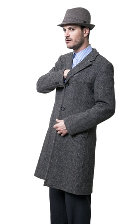 A person dressed in a gray overcoat and a gray hat. He seems to be very serious, wearing an intimidating facial experssion, reaching with his right hand to the overcoats inner pocket, as if to draw something out of it. Isolated on white background. photo