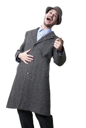 maching: A young adult male wearing an overcoat and a maching hat, looking and pointing at the camera bursting with laughter. Isolated on white background.