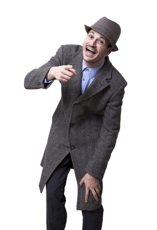 A young adult male wearing an overcoat and a maching hat, looking and pointing at the camera bursting with laughter. Isolated on white background.