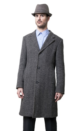be dressed in: A person dressed in a gray overcoat and a gray hat. He seems to be angry, wearing an intimidating facial experssion, as if very close to the edge of bursting in rage. Isolated on white background. Stock Photo