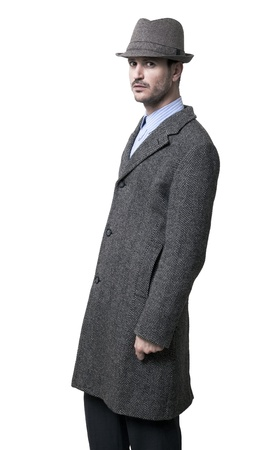 intimidating: A person dressed in a gray overcoat and a gray hat. He seems to be a bit angry, wearing an intimidating facial experssion, as if suspecing something which hes not particularly happy about. Isolated on white background. Stock Photo