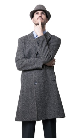 be dressed in: A young adult man dressed in a gray overcoat and a gray hat 1930s style, looking upwards with his finger on his lips, seems to be deep in thought. Isolated on white background. Stock Photo