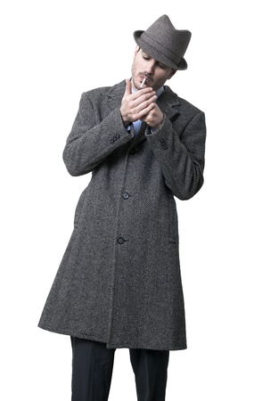 A person dressed in a gray overcoat and a gray hat. Hes in the process of lighting a cigarette. Isolated on white background. photo