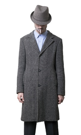 A person dressed in a gray overcoat and a gray hat that is completely hiding his eyes. Smoking a cigarette. Isolated on white background. photo