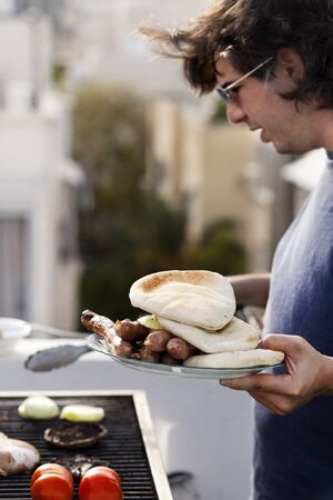 early 30s: Early 30s caucasian man loading a plate with the cooked items from the Sausages, onion slices and pita bread that are getting ready on an outdoor barbecue grill. Stock Photo