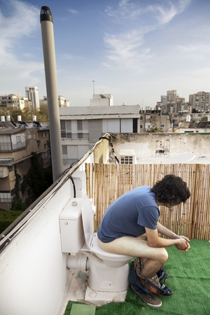 Caucasian adult man in his early 30s seems to be very concentrated in using an outdoor rooftop toilet. photo