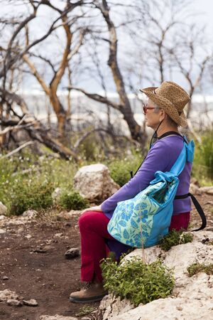 late 60s: Senior adult woman in her late 60s sitting on a rock in the middle of the wilderness, taking a break from walking and absorbing the powerful silent nature surrounding her. Stock Photo