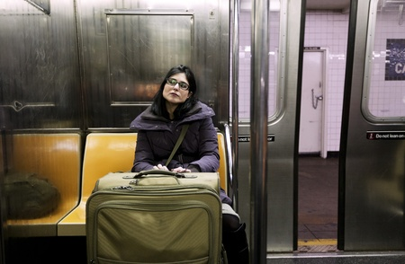 An adult woman with luggage sitting in the Brookly bound (downtown) A train subway in Manhattan, the door closing and train about to depart the station. photo