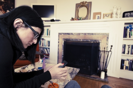 early 30s: An adult caucasian woman in her early 30s using her smartphone while sitting at a living room. Vintage coloring applied.
