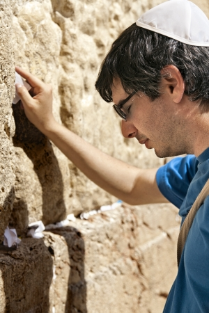 yamaka: A Jewish adult (early 30s) caucasian man concentrated in prayer in front of the wailing wall in the old city of Jerusalem, just before placing his wish note in the cracks between the giant stones.