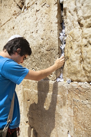 yamaka: A Jewish adult (early 30s) caucasian man concentrated in prayer in front of the wailing wall in the old city of Jerusalem, just before placing his wish note in the crack between the giant stones.