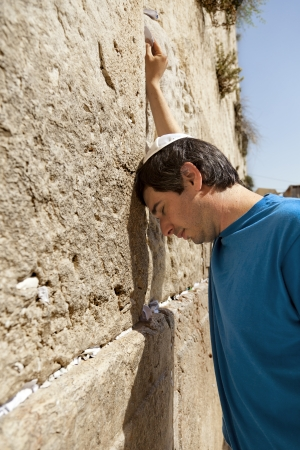 early 30s: A Jewish adult (early 30s) caucasian man concentrated in prayer in front of the wailing wall in the old city of Jerusalem, just before placing his wish note in the crack between the giant stones.