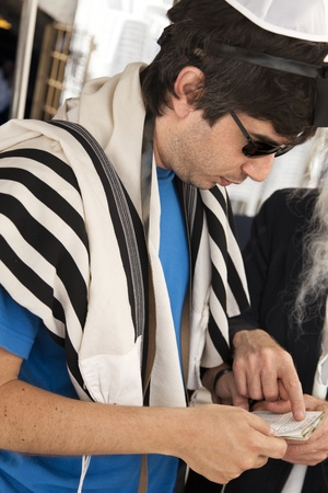 phylacteries: An adult Caucasian Jewish man wearing a praying shawl, Yarmulke and Phylacteries, while being helped by a Rabbi with praying. This man is  Stock Photo