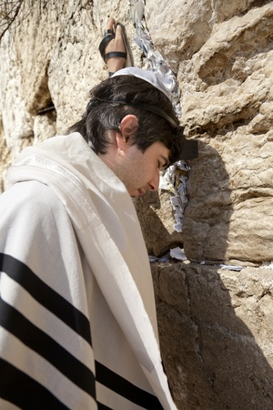 phylacteries: A Jewish adult (early 30s) Caucasian man wearing a Jewish praying shawl, Yarmulke and Phylacteries on his head and left hand; concentrated in prayer in front of the  holyWestern Wall (aka Wailing Wall) in the old city of Jerusalem, Israel.