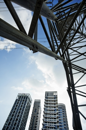 sofisticated: View at a high-voltage electricity pylon from directly below, which deconstructs the subject from its function and treats it as a mere sofisticated geometric abstract. A cluster of luxury apartment buildings seen in the background.