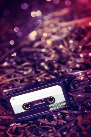 Black recordable plastic audio cassette resting on a large amount of magnetic audio tape  Selective focus on foreground  photo