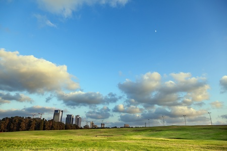ramat aviv: Bright green grassy hill at a park, with a line of dark green trees bordering the park from the concrete urban scenery, on the background of cloudy afternoon sky. Stock Photo