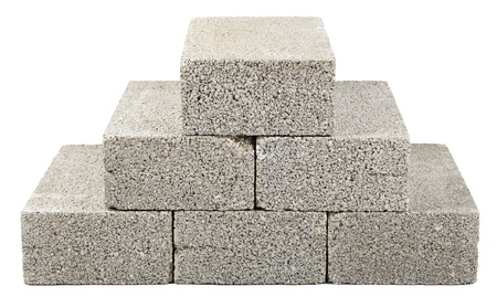 Six gray concrete construction blocks (a.k.a. cinder block, breeze block, cement block, foundation block, besser block; professional term: Concrete Masonary Unit - CMU) stacked together in the shape of a pyramid. Isolated on white background.
