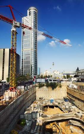 construction site: The initial stage of foundations in a construction site of a future skyscraper, with a tall derrick crane and skyscraper rising high above. Shot in downtown Ramat-Gan, Israel.