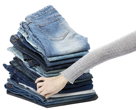 Woman's hand fumbling through a stack of various pairs of jeans pants.  Isolated on white background. photo