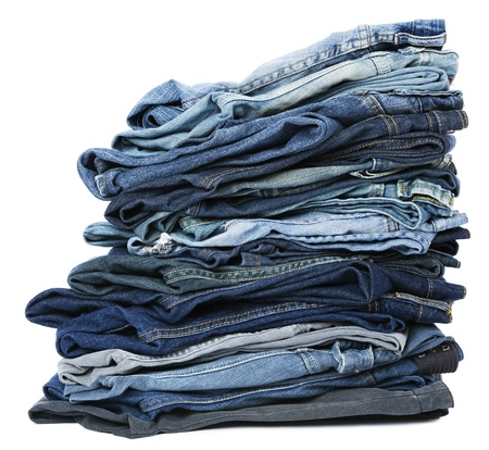 A stack of various pairs of jeans pants isolated on white background. photo