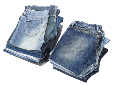 Two stacks of various pairs of jeans pants isolated on white background. photo