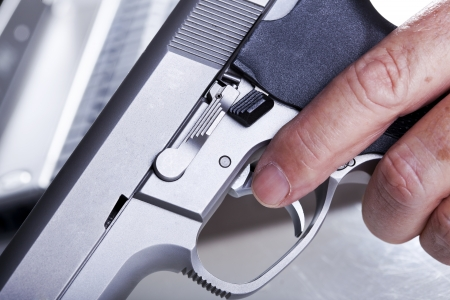VExtreme close up of a left hand of a mature adult man holding a 9mm handgun with his finger on the trigger, and a defocused laptop computer in the background. Backlit. Shallow depth of field. photo