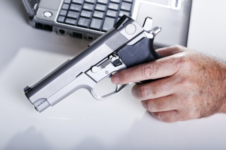 The left hand of a mature adult man holding a 9mm handgun, and a defocused laptop computer in the background. Backlit. Shallow depth of field.