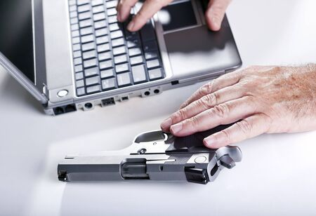 backlit keyboard: The hands of a mature adult man are in the middle of what seems to be hacking into a laptop computer in a hostile environment. His left hand resting on a 9mm handgun while his right is typing on the laptops keyboard. Backlit, Shallow depth of field.