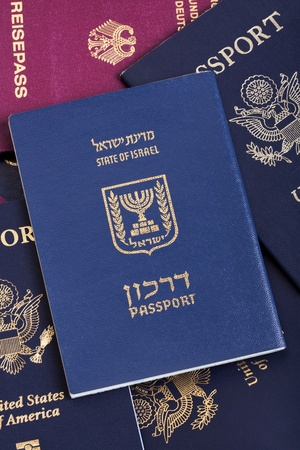 An Israeli passport resting on a stack of American and German passports. photo