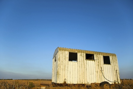beaten up: A deserted wreck of an old beaten up trailer in the middle of a harvested field in the very late hours of the afternoon.  Stock Photo