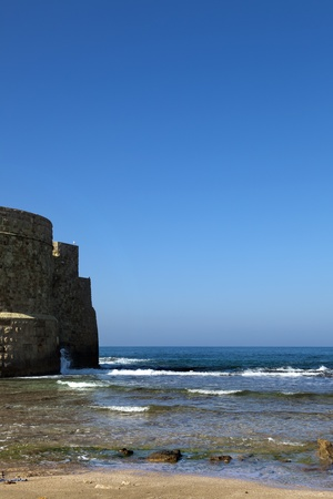 fortified wall: Part of the fortified wall surrounding the ancient city of Acco (Israel), bordering with the shore of the Mediterranean sea, on a clear spring day.