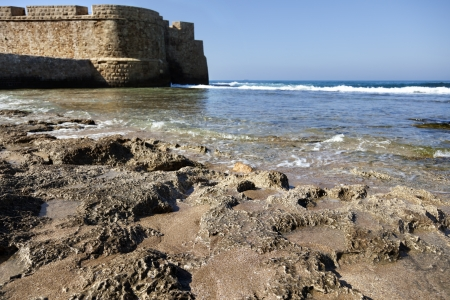 fortified wall: Part of the fortified wall surrounding the ancient city of Acco (Israel), bordering with the rocky shore of the Mediterranean sea, on a clear spring day. Stock Photo