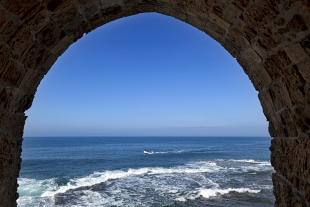 fortified wall: View at the Mediterranean sea with a fishermans boat from within an arched window set in the fortified wall surrounding the old town of Acco (Acre) in Israel.