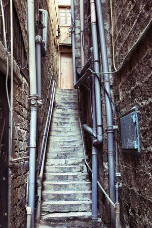 vertica: Narrow alley with pipes covered walls ends in a flight of stairs leading to an anonoymous door. Stock Photo
